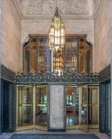 A carving of Mercury stands at the middle of the two banks of revolving doors at the entry to 111 Sutter Sreet.