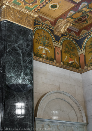 A close up of some of the painted details on the lobby ceiling, framed by a marble column.