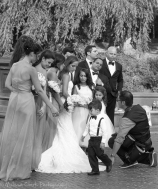 A wedding party gets ready to pose for photographs by the lake.